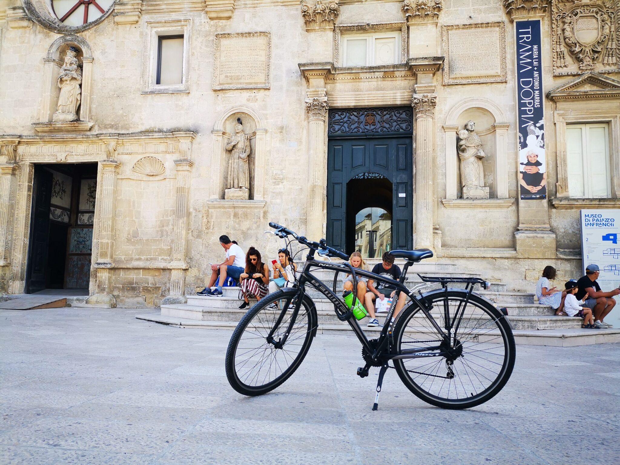 Ingresso di Palazzo Lanfranchi, con bici e turisti in pausa